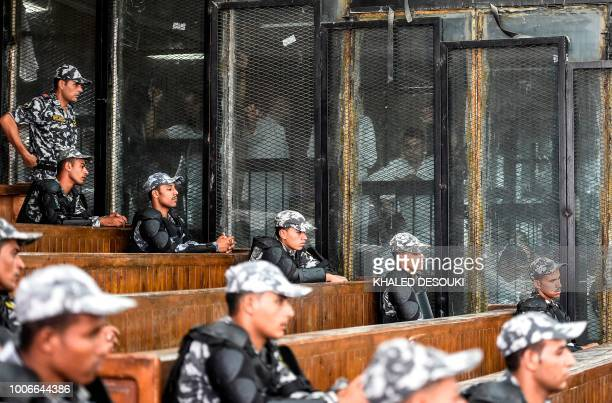 TOPSHOT Members of Egypt's banned Muslim Brotherhood are seen inside a glass dock during their trial in the capital Cairo on July 28 2018 An Egyptian...
