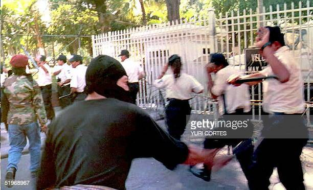 Members of El Salvador's National Civil Police run for cover behind the security fence at the presidential residence in San Salvador 27 January 1995...