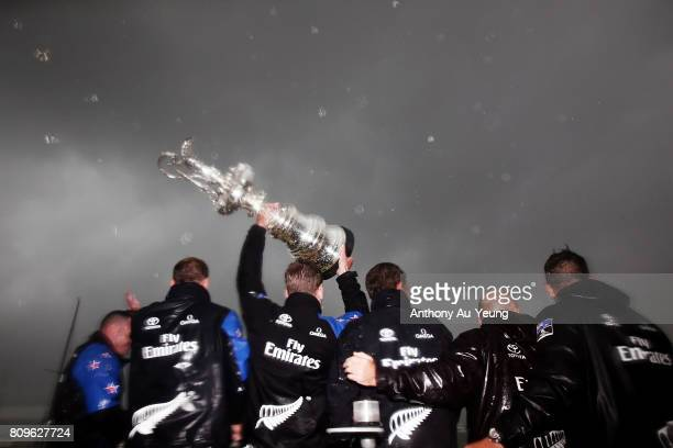 Members of Emirates Team New Zealand lift the America's Cup trophy in celebration during the Team New Zealand Americas Cup Welcome Home Parade on...