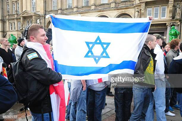 Members of English Defence League hold an Israeli flag during a demonstration in the city centre of Leeds on October 31 2009 The EDL slogan is that...