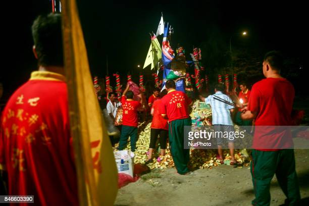 Members of ethnic Chinese make a last preparation in front of gods of ghost before being set on fire near the chinese temple during the Hungry Ghost...