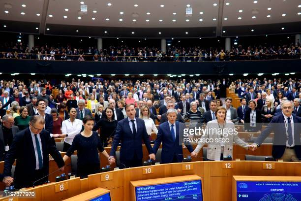 Members of European Parliament hold hands and sing after ratifying the Brexit deal during a plenary session at the European Parliament in Brussels on...