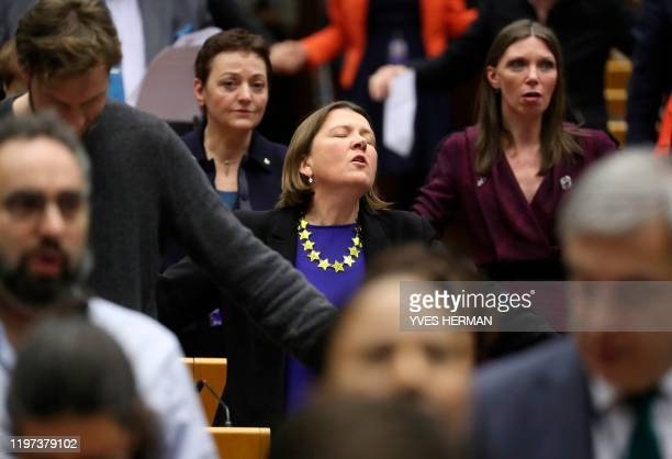 Members of European Parliament react after ratifying the Brexit deal during a plenary session at the European Parliament in Brussels on January 29,...