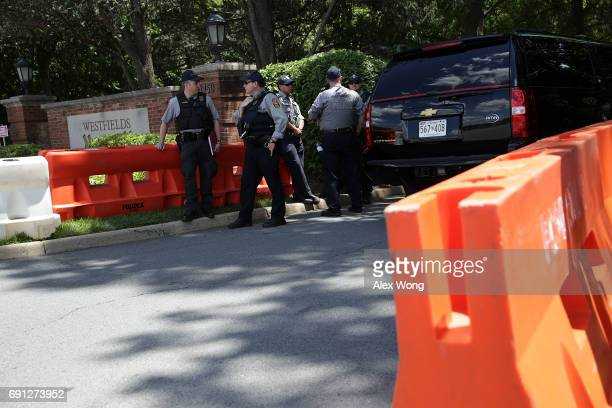 Members of Fairfax County Police stand guard at the entrance of Westfield Marriott Hotel where the Bilderberg Meeting takes place as a black SUV...