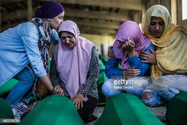 Members of family mourn over a coffin among 136 coffins of victims of the 1995 Srebrenica massacre in the hall at the Potocari cemetery and memorial...
