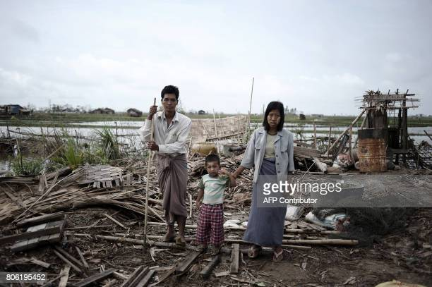 Members of family pose on the debris of their house detroyed by the cyclone Nargis in a village near Kyauktan in the delta region south of Yangon on...