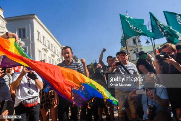 Members of far right associations burn a rainbow flag as they protest against the LGBT community on August 16, 2020 in Warsaw, Poland. At the same...
