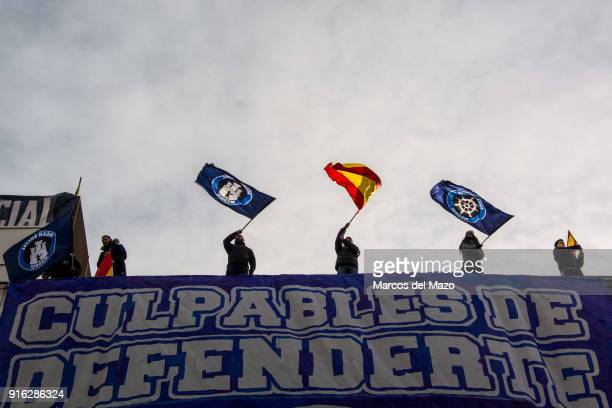 Members of far right group Hogar Social Madrid wave flags in the rooftop of occupied building as police arrives for their eviction which finally has...