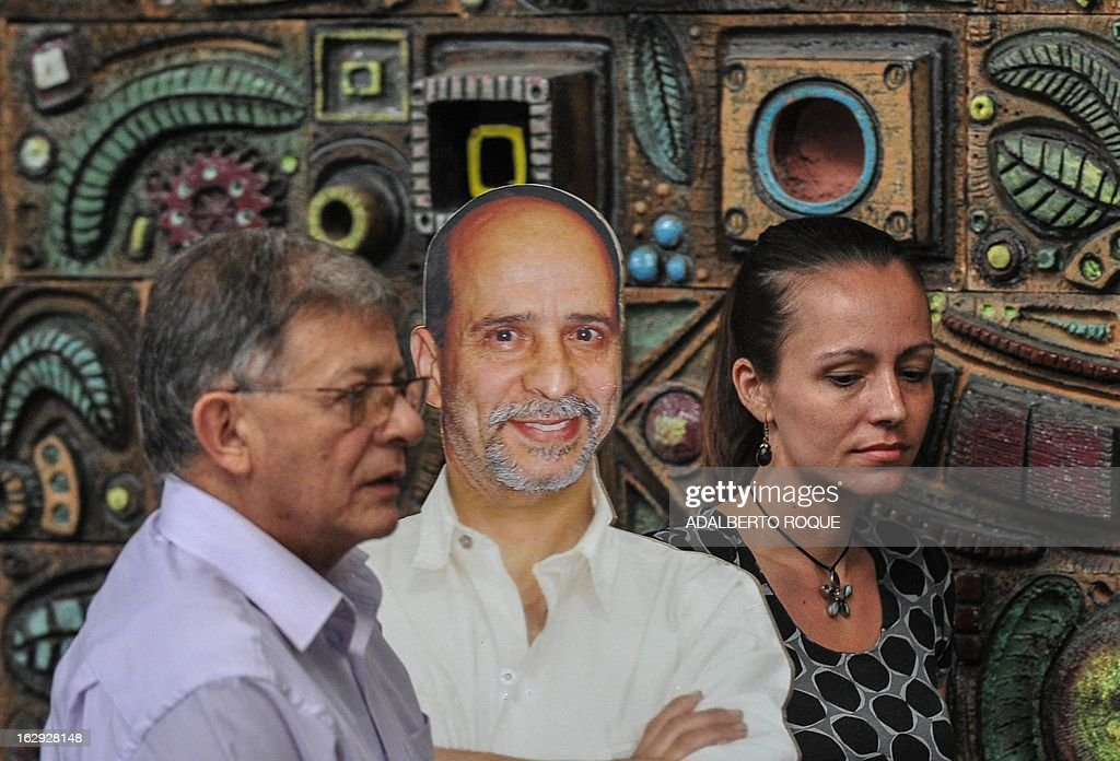 Members of FARC-EP leftist guerrillas delegation Commander Rodrigo Granda (L) and Dutch guerrilla fighter Tanja Nijmeijer (R) pass by a picture of Commander Simon Trinidad (in prison in The United States) as they arrive at Convention Palace in Havana to deliver a press conference on March 1, 2013.