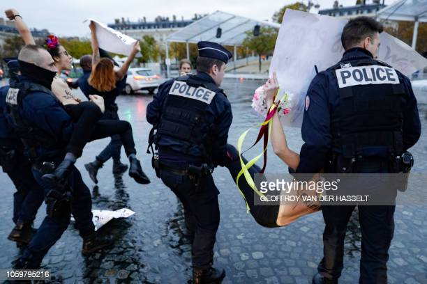 Members of feminist movement Femen are evacuated by the police after demonstrating in front of the Arc de Triomphe on November 10 as several leaders...