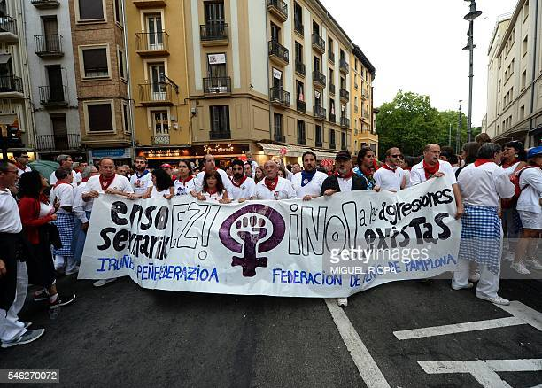 Members of festive groups march with a banner as they protest against the growing number of sexual assaults during the San Fermin bull run festival...