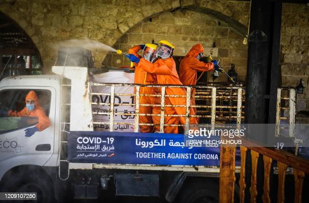 Members of Free Patriotic Movement a political party run by the Lebanese president's soninlaw disinfect a restaurant in Lebanon's northern coastal...