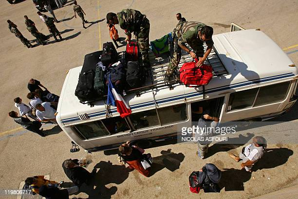 Members of French Commando Hubert load suitcases onto a bus as they secure an evacuation of foreign nationals from the southern town of Nabatiyeh to...