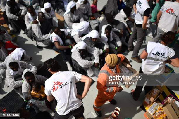 TOPSHOT Members of French NGO Medecins Sans Frontieres and SOS Mediterranee distribute food to migrants and refugees aboard the rescue ship Aquarius...