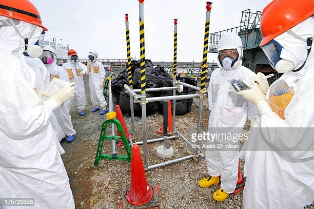 Members of Fukushima Prefecture panel inspects th well that higher radioactive water were detected at the crippled Fukushima Daiichi Nuclear Power...