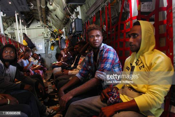 Members of Fula'aro male panpipe performers and dancers of the Solomon Islands Cultural Group take their seats aboard a RAAF Hercules C130J bound for...