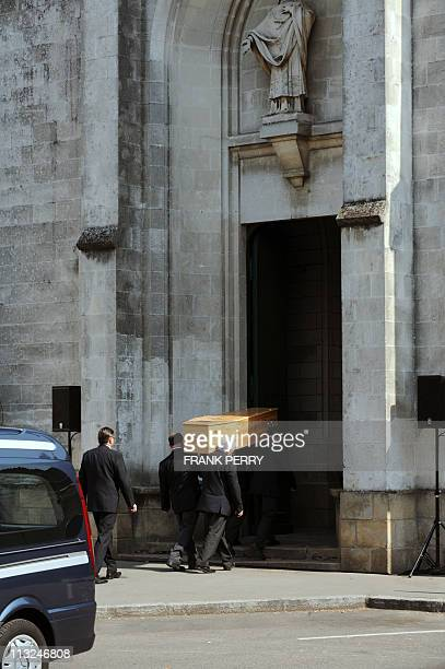 Members of funeral services carry a coffin into the church of Saint Felix in the French western city of Nantes on April 28 before the funeral...