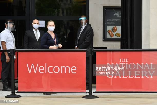 Members of gallery staff wearing protective face shields and face coverings wait to welcome members of the media for a press preview at the National...