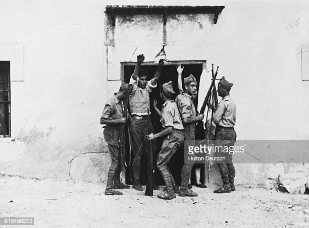 Members of General Franco's nationalist troops searching a villager at Burgos during the Civil War