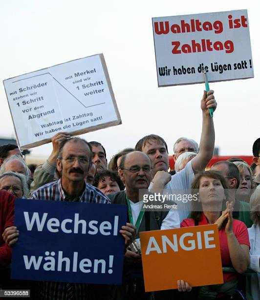 Members of German Christian Democrats show a sign that is pro the politics of the Candidate Chancellor Angela Merkel of the German Christian...