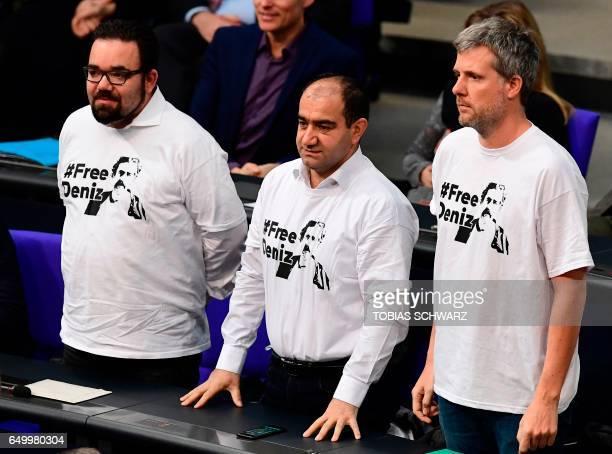 Members of German environmental Greens party 'Die Gruenen' Chris Kuehn Ozcan Mutlu and Dieter Janecek stand up wearing a shirt reading 'Free Deniz'...