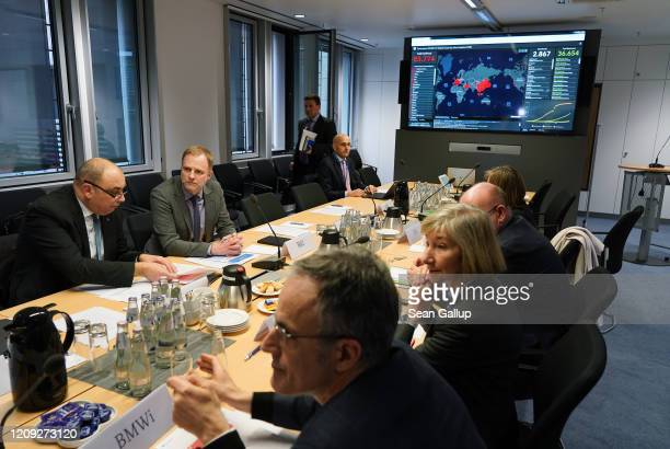 Members of Germany's coronavirus emergency task force sit down for a work session while a monitor shows the global spread and human toll of the virus...