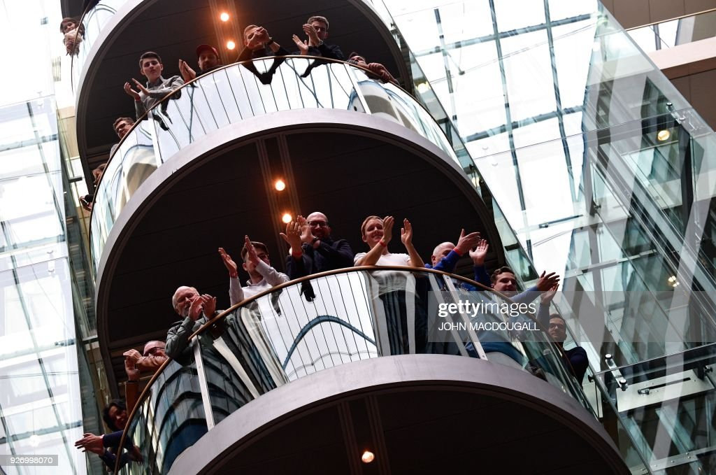 Members of Germany's Social Democrats (SPD) party applaud during a press conference as the result is announced of the SPD party members' referendum on whether or not to join a new coalition government with German Chancellor Angela Merkel's conservatives, on March 4, 2018 at the SPD headquarters in Berlin. The members of Germany's second biggest party have in their high-stakes referendum approved a plan to join Chancellor Angela Merkel's coalition. The make or break vote was the last hurdle in the way of Merkel's fourth term in office and essentially ends a political stalemate that has plagued the country since September's inconclusive elections. / AFP PHOTO / John MACDOUGALL