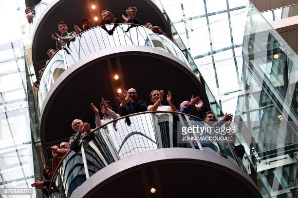 Members of Germany's Social Democrats party applaud during a press conference as the result is announced of the SPD party members' referendum on...