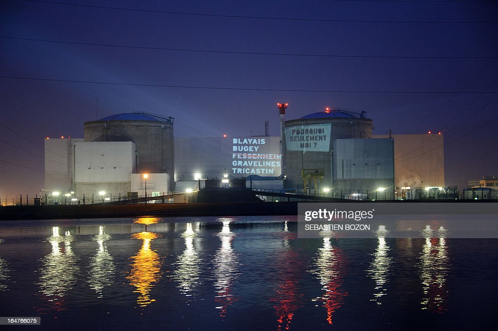 Members of Greenpeace projects texts reading: Blayay, Bugey, Fessenheim, Gravelines, Tricastin, why me only?, on the nuclear powerplant of Fessenheim, in eastern France on March 28, 2013.