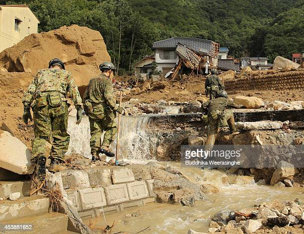Members of Ground Self-Defense Force officers continue the search for missing people among the debris of house destroyed by a landslide caused by...