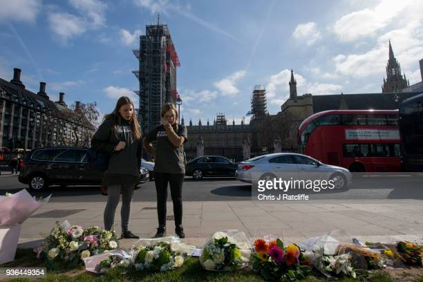Members of group Victim Support look at floral tributes in Parliament Square on the first anniversary of the Westminster Bridge terror attack on...