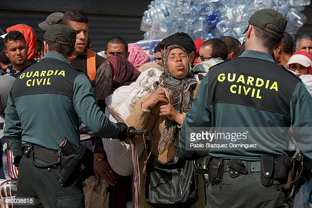 Members of Guardia Civil hold back a crowd of people trying to cross through the Beni Enzar border point to Morocco once the gates opened again on...