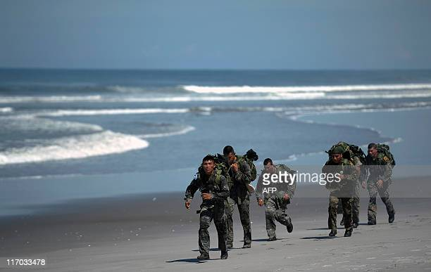 Members of Guatemala's Kaibiles commando group take part in a competition in La Costa del Sol beach 61 km south from San Salvador El Salvador on June...