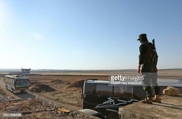 A members of Hayat Tahrir alSham group led by Syria's former AlQaeda affiliate watches a bus gets ready to enter the towns of Fuaa and Kefraya to...