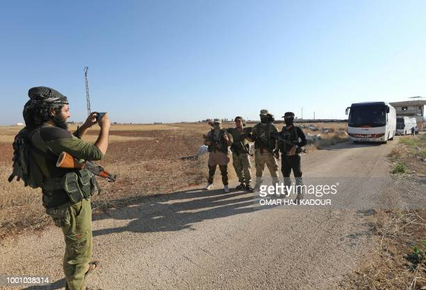 Members of Hayat Tahrir alSham group led by Syria's former AlQaeda affiliate get their picture taken in front of a convoy of busses geting ready to...