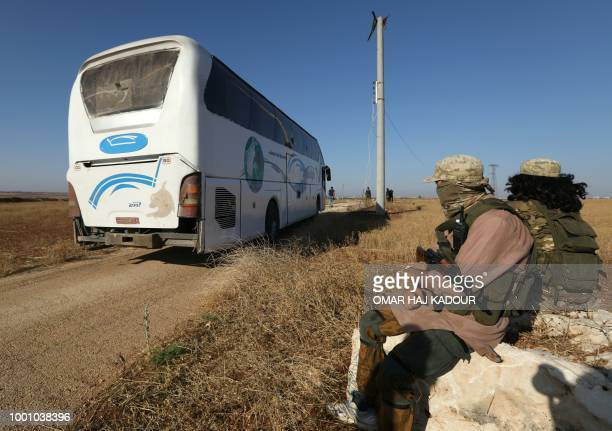 Members of Hayat Tahrir alSham group led by Syria's former AlQaeda affiliate watch as busses get ready to enter the towns of Fuaa and Kefraya to...
