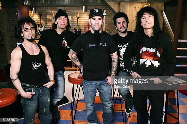 Members of heavy metal band Anthrax Danny Spitz, Frank Bello, Scott Ian, Charlie Benante, and Joey Belladonna pose for a photo onstage during an...