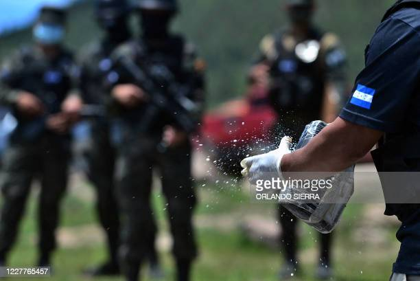 Members of Honduras' Technical Bureau for Criminal Investigation prepare to burn some 250k of cocaine, seized last May, on July 24, 2020 in...
