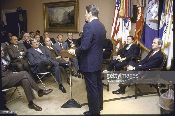 Members of House Armed Services Committee incl Reps Les Aspin William Dickinson listening to President Reagan speak with Defense Secretary Weinberger...