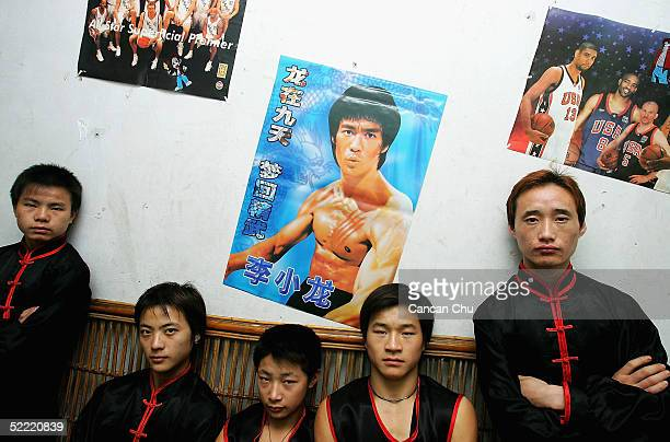 Members of Huang Feihong martial arts team pose for pictures under a poster of the famous Kung Fu movie star Bruce Lee at their dormitory on February...