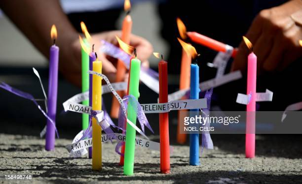 Members of human rights group, Volunteers Against Crime and Corruption , light candles with names of those killed during the shooting at Sandy Hook...