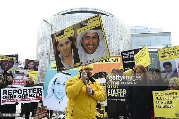 Members of Human rights NGO Amnesty International hold up portraits of jailed Saudi blogger Raif Badawi and Saudi human rights activist and lawyer...