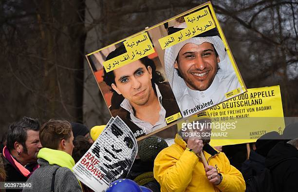 Members of Human rights NGO Amnesty International hold up portraits of jailed Saudi blogger Raif Badawi and Saudi human rights activist and lawyer...