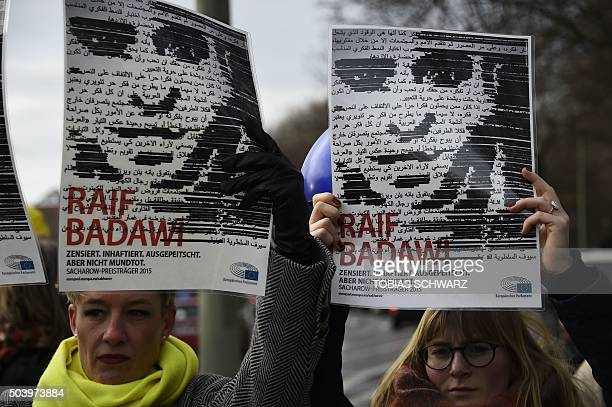 Members of Human rights NGO Amnesty International hold up portraits of jailed Saudi blogger Raif Badawi as they demonstrate in front of the embassy...