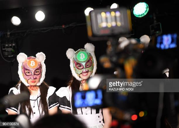 TOPSHOT Members of idol group Kasotsuka Shojo wearing bitcoin masks look on during an interview following their live stage performance in Tokyo on...