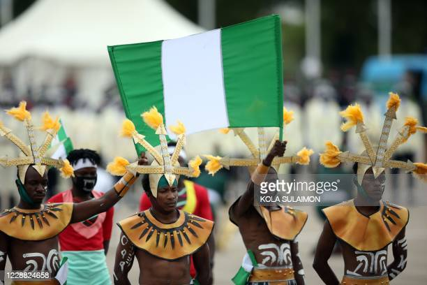 Members of Independence Band display the Nigerian national flag at the Eagles Square in Abuja, Nigeria during the countrys 60th Independence...