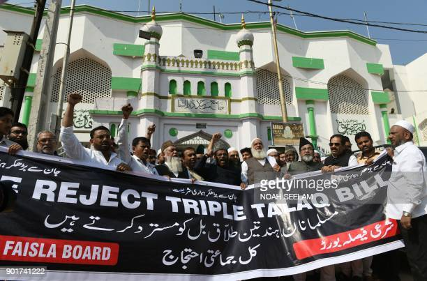 Members of Indian Muslim organisations shout slogans as they hold a banner against a proposed 'Triple Talaq Bill' during a protest in Hyderabad on...