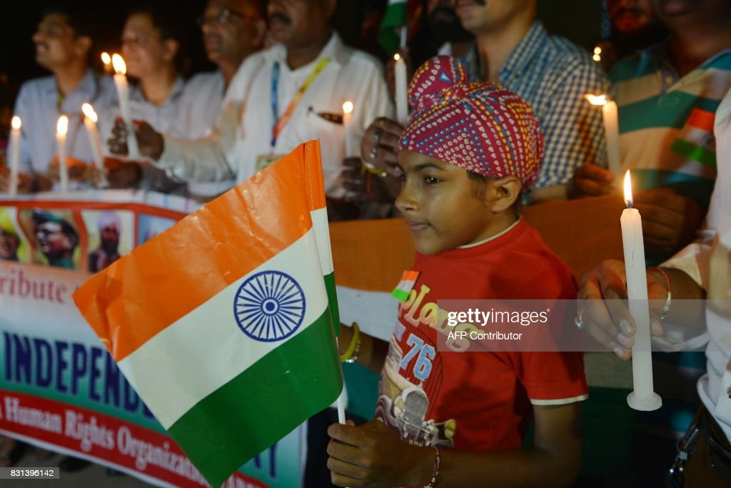 Members of India`s Akhil Bhartiya Human Rights Organisation hold lighted candles as they pay tribute to Indian freedom fighters at the India Pakistan.