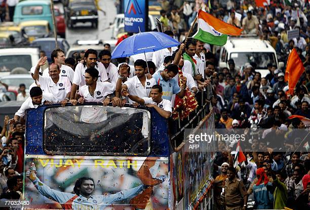 Members of India's cricket team greet crowds from an open topped bus on the way to a special falicitatory function at the Wankhede stadium in Mumbai,...