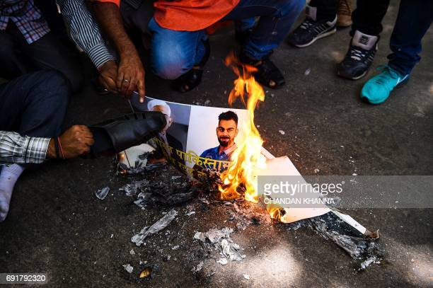 Members of India's rightwing Hindu Sena group burn a poster bearing the images of Indian cricket team captain Virat Kohli and president of the Board...